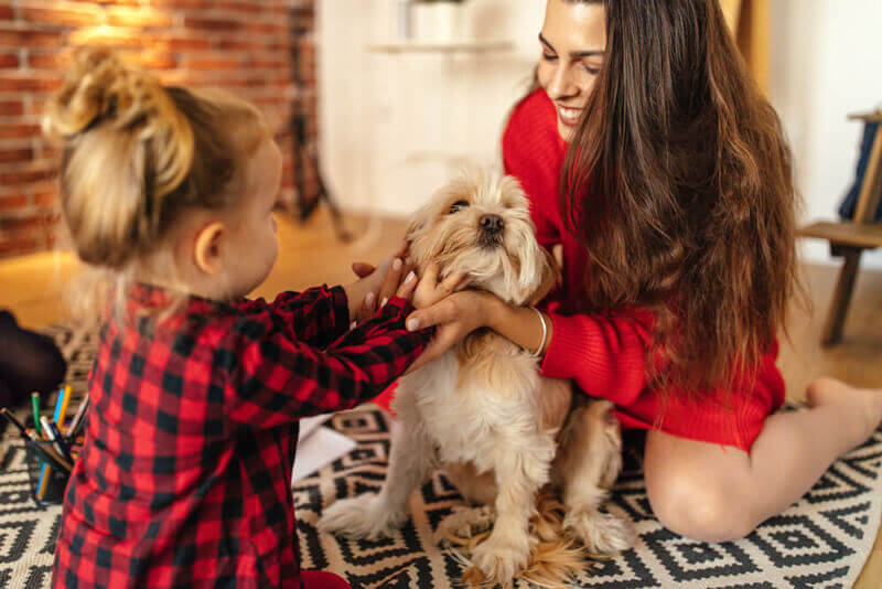 Woman spending time with daughter and dog.